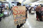 FILE - In this Aug. 13, 2019, file photo, a protester shows a placard to stranded travelers during a demonstration at the Airport in Hong Kong. Visitor numbers to Hong Kong fell by nearly 40% in the second half of last year amid clashes between police and anti-government protesters. (AP Photo/Kin Cheung, File)