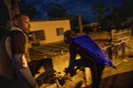 Nicholas Bingham, left, and Delroy Gooden, prepare to climb over a wall to go night spearfishing, which is banned, in Stewart Town, Jamaica, Friday, Feb. 15, 2019. Bingham and Gooden say they resort to illegal night spearfishing to make up for lost wages from the sanctuary's restrictions. Some fish and other sea creatures sleep in the reef at night making them easier to catch than during the day. (AP Photo/David Goldman)