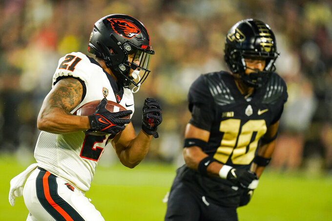 Oregon State running back Trey Lowe (21) tries to get past Purdue safety Cam Allen (10) during the first half of an NCAA college football game in West Lafayette, Ind., Saturday, Sept. 4, 2021. (AP Photo/Michael Conroy)