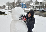 Blake Wise applies the head of the snowman that he and Brianna Atwood built along South 7th Street in Terre Haute, Ind., on Saturday, Jan. 12, 2019. A massive winter snowstorm making its way across the Midwest and into the Mid-Atlantic region blanketed most of Missouri and several other states. (Austen Leake/The Tribune-Star via AP)