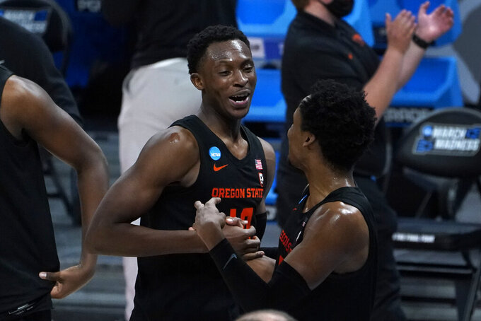 Oregon State forward Warith Alatishe, left, and Oregon State guard Gianni Hunt (0) celebrate after beating Tennessee 70-56 in a men's college basketball game in the first round of the NCAA tournament at Bankers Life Fieldhouse in Indianapolis, Friday, March 19, 2021. (AP Photo/Paul Sancya)