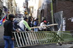 Supporters of former President Evo Morales bring down a barricade that was keeping them from reaching the presidential palace, during clashes with police in La Paz, Bolivia, Friday, Nov. 15, 2019. Morales stepped down on Sunday following nationwide protests over suspected vote-rigging in an Oct. 20 election in which he claimed to have won a fourth term in office. An Organization of American States audit of the vote found widespread irregularities. (AP Photo/Natacha Pisarenko)