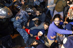 Anti-government protesters lie on a road, as they scream and hold each others while riot police try to remove them and open the road, in Beirut, Lebanon, Wednesday, Dec. 4, 2019. Protesters have been holding demonstrations since Oct. 17 demanding an end to widespread corruption and mismanagement by the political class that has ruled the country for three decades. (AP Photo/Bilal Hussein)