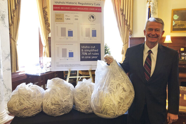 FILE - In this Dec. 4, 2019 file photo Idaho Republican Gov. Brad Little holds a bag of shredded paper in the Idaho Statehouse, in Boise, Idaho, representing what he says are thousands of pages of state regulations he's cut or simplified. Idaho officials cut a nuclear deal with the U.S. Department of Energy to allow in research quantities of spent nuclear fuel, Medicaid expansion survived a court challenge and lawmaker antipathy, and  Little cut or simplified what he says are 75% of the state's administrative rules.   (AP Photo/Keith Ridler,File)
