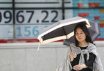 A woman walks by an electronic stock board of a securities firm in Tokyo, Tuesday, June 18, 2019. Stocks in Asia mostly advanced Tuesday ahead of interest rate decisions by the U.S. Federal Reserve and other central banks. (AP Photo/Koji Sasahara)