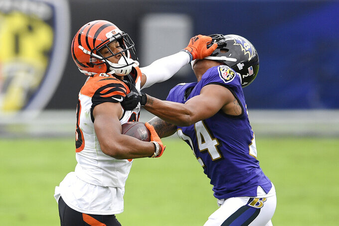 Cincinnati Bengals wide receiver Tyler Boyd, left, applies a stiff arm on Baltimore Ravens cornerback Marcus Peters during the first half of an NFL football game, Sunday, Oct. 11, 2020, in Baltimore. (AP Photo/Nick Wass)