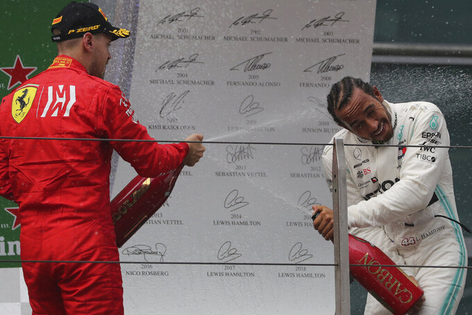 Mercedes driver Lewis Hamilton of Britain is sprayed with champagne by Ferrari driver Sebastian Vettel of Germany during the award ceremony after the Chinese Formula One Grand Prix at the Shanghai International Circuit in Shanghai on Sunday, April 14, 2019. (AP Photo/Ng Han Guan)