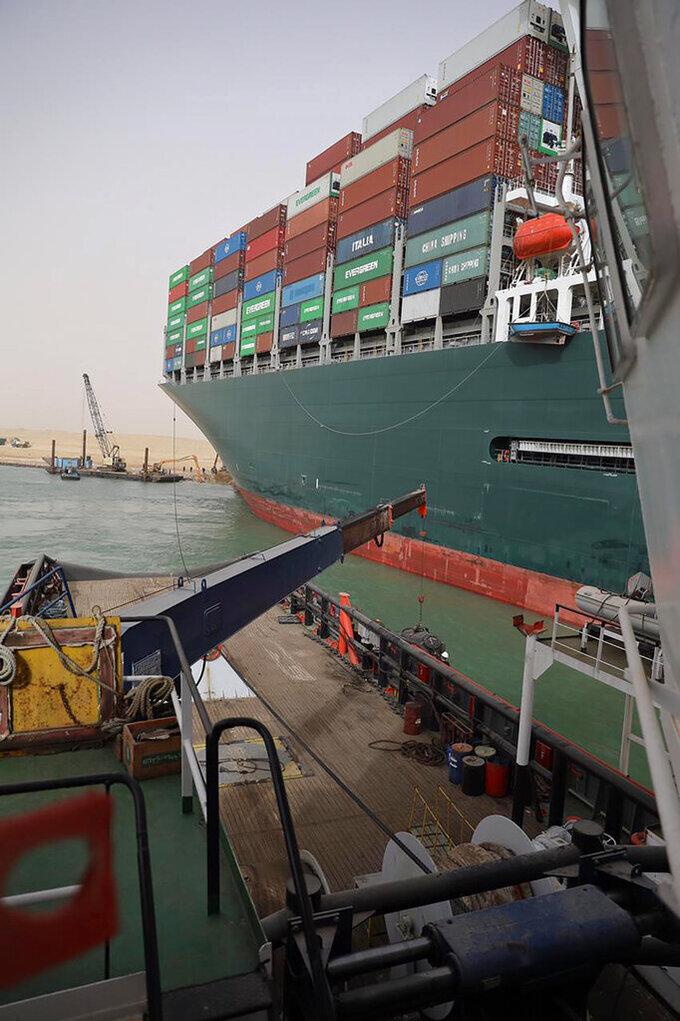 In this photo released by the Suez Canal Authority on Thursday, March 25, 2021, the Ever Given, a Panama-flagged cargo ship, after it become wedged across the Suez Canal and blocking traffic in the vital waterway, is seen from another vessel. An operation is underway to try to work free the ship, which further imperiled global shipping Thursday as at least 150 other vessels needing to pass through the crucial waterway idled waiting for the obstruction to clear. (Suez Canal Authority via AP)