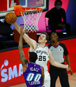 San Antonio Spurs' Jakob Poeltl (25) blocks a shot from Utah Jazz's Jordan Clarkson during the first half of an NBA basketball game Friday, Aug. 7, 2020, in Lake Buena Vista, Fla. (Kevin C. Cox/Pool Photo via AP)