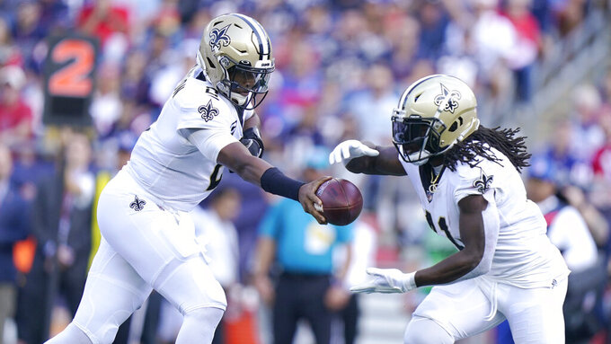 New Orleans Saints quarterback Jameis Winston, left, hands the ball to running back Alvin Kamara during the first half of an NFL football game against the New England Patriots, Sunday, Sept. 26, 2021, in Foxborough, Mass. (AP Photo/Steven Senne)