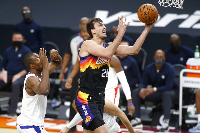 Phoenix Suns forward Dario Saric (20) drives to the basket past the defense of as Los Angeles Clippers center Serge Ibaka, left, during the second half of an NBA basketball game Sunday, Jan. 3, 2021, in Phoenix. (AP Photo/Ralph Freso)