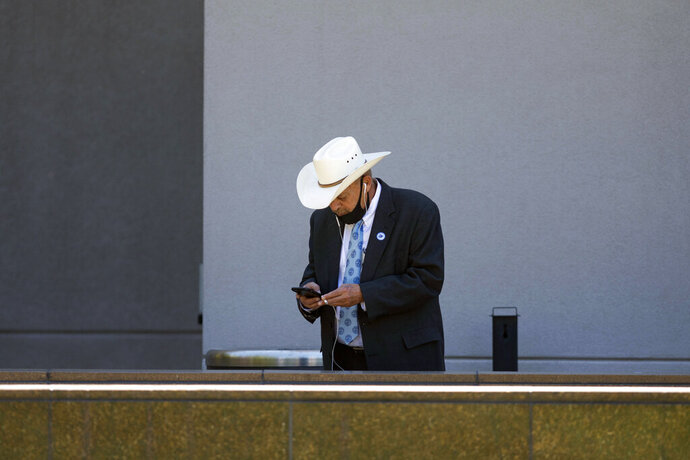 Nevada Assemblyman Jim Wheeler looks at this cellphone outside the Nevada Legislature before the Assembly gaveled in for the fourth day of the 31st Special Session of the Nevada Legislature in Carson City, Nev., Saturday, July 11, 2020. (David Calvert/The Nevada Independent via AP, Pool)