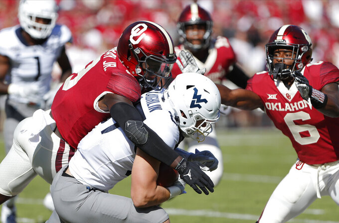 Oklahoma linebacker Kenneth Murray (9) tackles West Virginia wide receiver Freddie Brown (17) during the first half of an NCAA college football game in Norman, Okla., Saturday, Oct. 19, 2019. (AP Photo/Alonzo Adams)