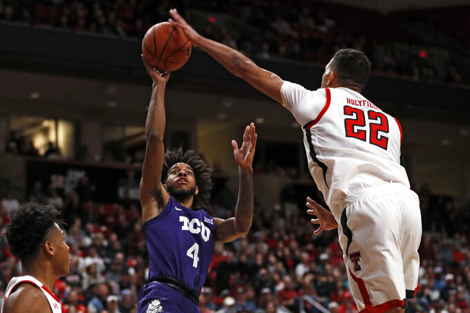 Texas Tech's TJ Holyfield (22) blocks a shot by TCU's PJ Fuller (4) during the first half of an NCAA college basketball game Monday, Feb. 10, 2020, in Lubbock, Texas. (AP Photo/Brad Tollefson)