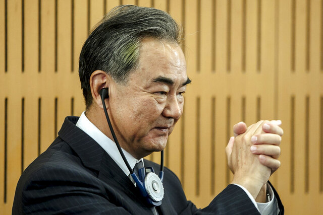 Chinese Foreign Minister Wang Yi greets the audience prior a press conference at the Institute for International Relations in Paris, Sunday, Aug. 30, 2020. Chinese Foreign Minister Wang Yi is in France as part of a five-country trip to Europe, his first since the coronavirus pandemic. (AP Photo/Kamil Zihnioglu)