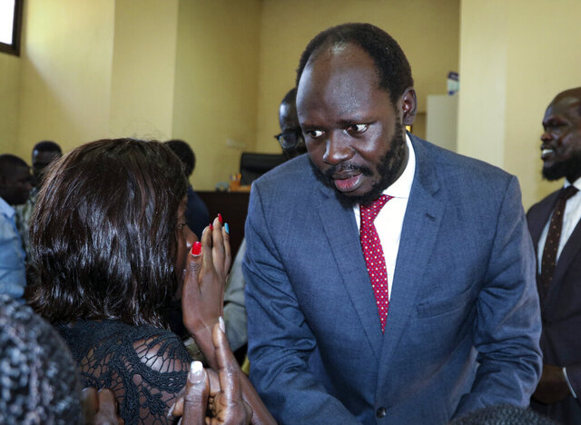 FILE - In this Tuesday, June 11, 2019 file photo, prominent South Sudanese activist and economist Peter Biar Ajak prepares to embrace his wife Nyathon Hoth Mai, left, as she weeps after he was sentenced to two years in prison, in a courtroom in the capital Juba, South Sudan. A lawyer said Friday, Jan 3, 2020 that the prominent South Sudan activist and economist has not been freed from prison despite being pardoned in a presidential decree. (AP Photo/Sam Mednick, File)