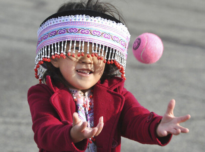 Four-year-old Vania Yang peers through her beaded hat to play the traditional game of Pov Pob during the first day of the Hmong New Year celebration at the Fresno Fairgrounds, Thursday Dec. 26, 2019. (John Walker/The Fresno Bee via AP)