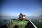 A fisherman rows his boat after casting his nets for the night, in Lake Chivero, west of the capital Harare, in Zimbabwe Tuesday, Sept. 10, 2019. Former president Robert Mugabe, who enjoyed strong backing from Zimbabwe's people after taking over in 1980 but whose support waned following decades of repression, economic mismanagement and allegations of election-rigging, is expected to be buried on Sunday, state media reported. (AP Photo/Ben Curtis)