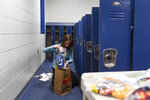 In this Monday, May 11, 2020 photo, Tracie Robinson, a seventh grade English teacher, empties students' lockers at Memorial Middle School in Sioux Falls, S.D. (Erin Bormett/The Argus Leader via AP)