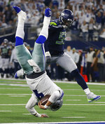 Dallas Cowboys quarterback Dak Prescott (4) flies for the goal line and makes a first down against Seattle Seahawks defensive end Frank Clark (55) during the second half of the NFC wild-card NFL football game in Arlington, Texas, Saturday, Jan. 5, 2019. (AP Photo/Ron Jenkins)