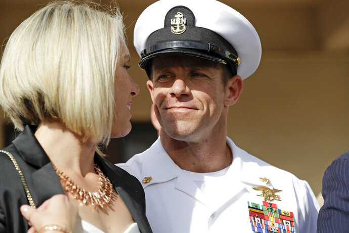 FILE - In this July 2, 2019 file photo, Navy Special Operations Chief Edward Gallagher, right, walks with his wife, Andrea Gallagher as they leave a military court on Naval Base San Diego, in San Diego. The Navy has dismissed charges against an officer for allegedly not reporting war crimes by Gallagher, who was later acquitted of murder. A Navy official with knowledge of the decision not authorized to speak publicly confirmed said charges against Lt. Jacob Portier were dropped Thursday, Aug. 1, 2019. (AP Photo/Gregory Bull, File)