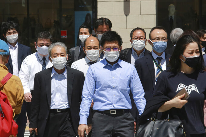 People wearing face masks to protect against the spread of the coronavirus walk on a street in Tokyo, Tuesday, April 20, 2021. (AP Photo/Koji Sasahara)