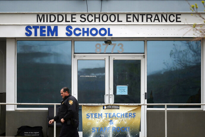 FILE - In this May 8, 2019, file photo, a Douglas County, Colo., Sheriff's Department deputy walks past the doors to the STEM School Highlands Ranch, in Highlands Ranch, Colo. A private security guard who officials say accidentally fired at a deputy and ended up wounding a student during a shooting at the school on May 7, 2019 was not supposed to be armed, The Colorado Sun reported. (AP Photo/David Zalubowski, File)