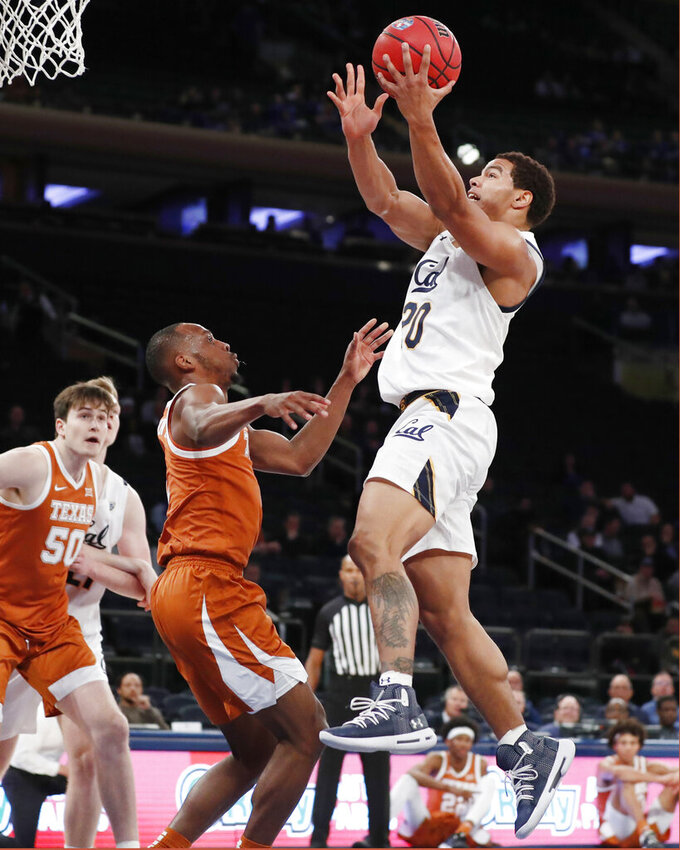 Texas guard Matt Coleman III, second from left, watches as California guard Matt Bradley (20) goes up for a layup with Texas center Will Baker (50) watching during the first half of an NCAA college basketball game in the 2K Empire Classic, Friday, Nov. 22, 2019, in New York. (AP Photo/Kathy Willens)