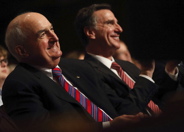 President of Indiana University Michael McRobbie, left, and Lee Feinstein, Dean for the Hamilton Lugar School of Global and International Studies, right, smile as they listen to Presidential nominee hopeful Pete Buttigieg at the IU Auditorium in Bloomington, Ind. Tuesday, June 11, 2019. McRobbie announced Friday, Aug. 14, 2020 that he plans to retire in June 2021 after a 14-year tenure as one of the school's longest-serving leaders. (Rich Janzaruk/The Herald-Times via AP)
