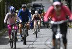People ride their bikes amid the new coronavirus pandemic, in the Los Chorros neighborhood of Caracas, Venezuela, Sunday, July 12, 2020. (AP Photo/Matias Delacroix)