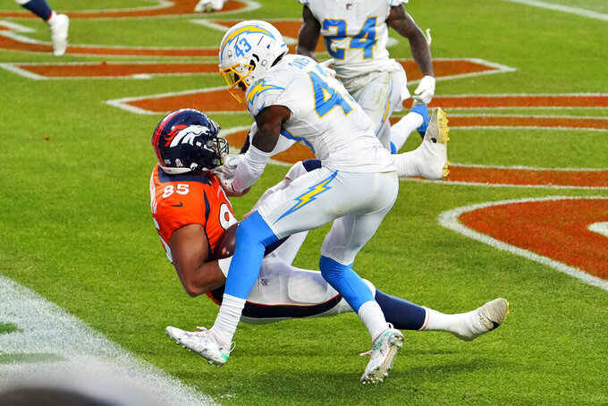 Denver Broncos tight end Albert Okwuegbunam (85) scores a touchdown as Los Angeles Chargers cornerback Michael Davis (43) defends during the second half of an NFL football game, Sunday, Nov. 1, 2020, in Denver. (AP Photo/Jack Dempsey)