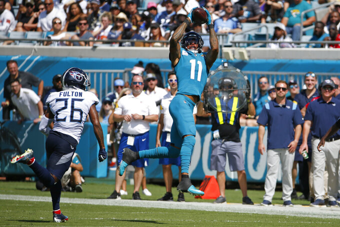 Jacksonville Jaguars wide receiver Marvin Jones (11) makes a reception in front of Tennessee Titans cornerback Kristian Fulton (26) during the first half of an NFL football game, Sunday, Oct. 10, 2021, in Jacksonville, Fla. (AP Photo/Stephen B. Morton)