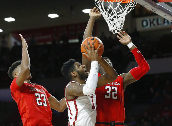 Oklahoma guard Rashard Odomes (1) shoots between Texas Tech guard Jarrett Culver (23) and center Norense Odiase (32) in the second half of an NCAA college basketball game in Norman, Okla., Saturday, Feb. 9, 2019. (AP Photo/Sue Ogrocki)