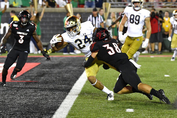 Notre Dame tight end Tommy Tremble (24) extends the ball across the goal line as Louisville safety Drew Brenowitz (38) tries to stop him during the second half of an NCAA college football game in Louisville, Ky., Monday, Sept. 2, 2019. Notre Dame won 35-17. (AP Photo/Timothy D. Easley)