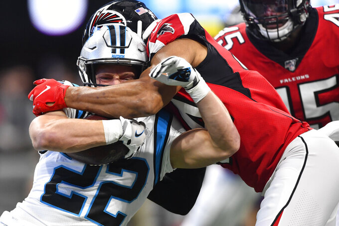 Carolina Panthers running back Christian McCaffrey (22) is hit by Atlanta Falcons defensive end Vic Beasley (44) during the first half of an NFL football game, Sunday, Dec. 8, 2019, in Atlanta. (AP Photo/John Amis)