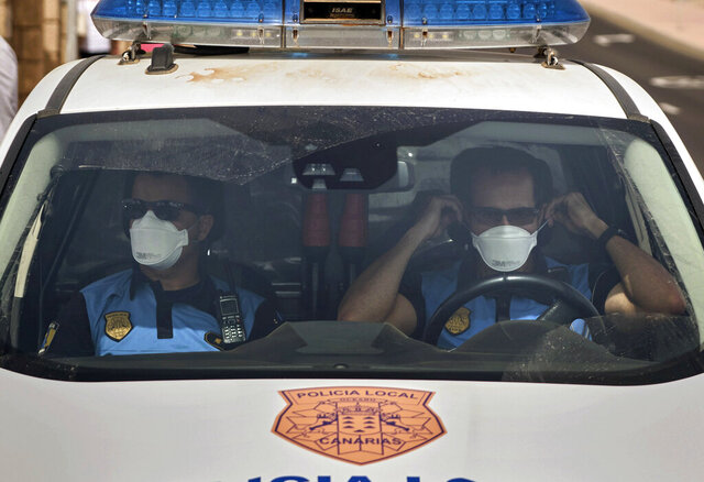 Spanish police officers patrol outside the H10 Costa Adeje Palace hotel in Tenerife, Canary Island, Spain, Tuesday, Feb. 25, 2020. Spanish officials say a tourist hotel on the Canary Islands has been placed in quarantine after an Italian doctor staying there tested positive for the new coronavirus. (AP Photo)