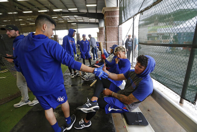 Texas Rangers minor league players Chris Seise, right, and Kevin Mendoza shake hands in greeting in the batting cages Thursday, March 12, 2020, in Surprise, Ariz. Major League Baseball is delaying the start of its season by at least two weeks because of the coronavirus outbreak and has suspended the rest of its spring training game schedule. (AP Photo/Elaine Thompson)