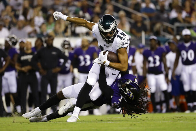 Philadelphia Eagles' JJ Arcega-Whiteside (19) is tackled by Baltimore Ravens' Maurice Canady (26) during the first half of a preseason NFL football game Thursday, Aug. 22, 2019, in Philadelphia. (AP Photo/Michael Perez)