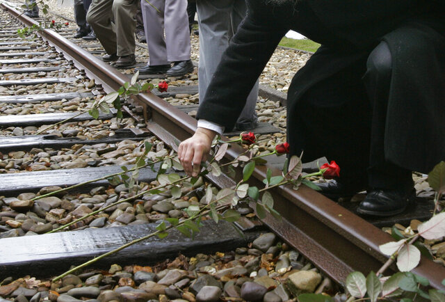 FILE - In this file photo dated Monday May 9, 2015, roses are symbolically placed on the railroad tracks at former concentration camp Westerbork, the Netherlands, remembering more than a hundred thousand Jews transported from Westerbork to Nazi death camps during WWII.  The NS railway company, announced that it will donate 5 million euros (dollars 5.6 million U.S. ) to Dutch Holocaust memorial centers as a gesture of collective recognition, but Jewish organizations criticized the company Monday June 29, 2020, for not adequately consulting them in discussions. (AP Photo/Peter Dejong, FILE)
