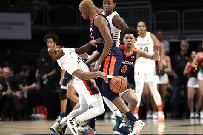 Miami guard Chris Lykes, left, falls to the court as he is fouled by Virginia forward Mamadi Diakite, center, during the first half of an NCAA college basketball game, Wednesday, March 4, 2020, in Coral Gables, Fla. (AP Photo/Lynne Sladky)