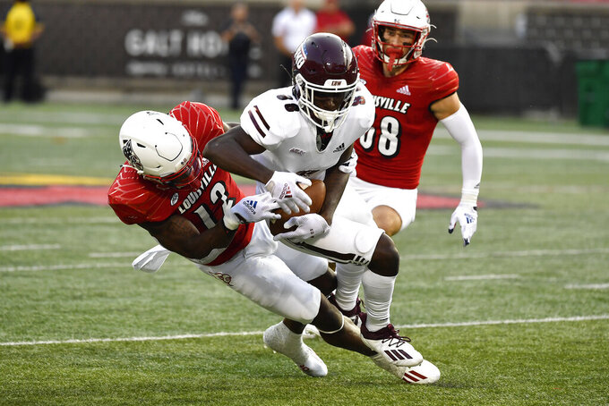Louisville defensive back Qwynnterrio Cole (12) attempts to strip the ball from Eastern Kentucky's Jaden Smith, center, during the first half of an NCAA college football game in Louisville, Ky., Saturday, Sept. 11, 2021. (AP Photo/Timothy D. Easley)