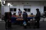 Customers wearing face masks against the spread of coronavirus, wait to buy potatoes at an open-air fruit and vegetable market in Athens, Monday, Nov. 23, 2020. Greece has seen a major resurgence of the virus after the summer, leading to dozens of deaths each day and thousands of new infections. (AP Photo/Thanassis Stavrakis)