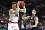 Gonzaga's Corey Kispert (24) drives around Saint Mary's Tommy Kuhse (12) in the first half of an NCAA college basketball game in the final of the West Coast Conference men's tournament Tuesday, March 10, 2020, in Las Vegas. (AP Photo/John Locher)
