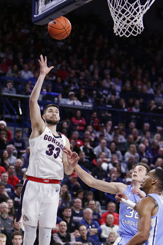 Gonzaga forward Killian Tillie, left, shoots over North Carolina guard Justin Pierce, center, during the second half of an NCAA college basketball game in Spokane, Wash., Wednesday, Dec. 18, 2019. Gonzaga won 94-81. (AP Photo/Young Kwak)