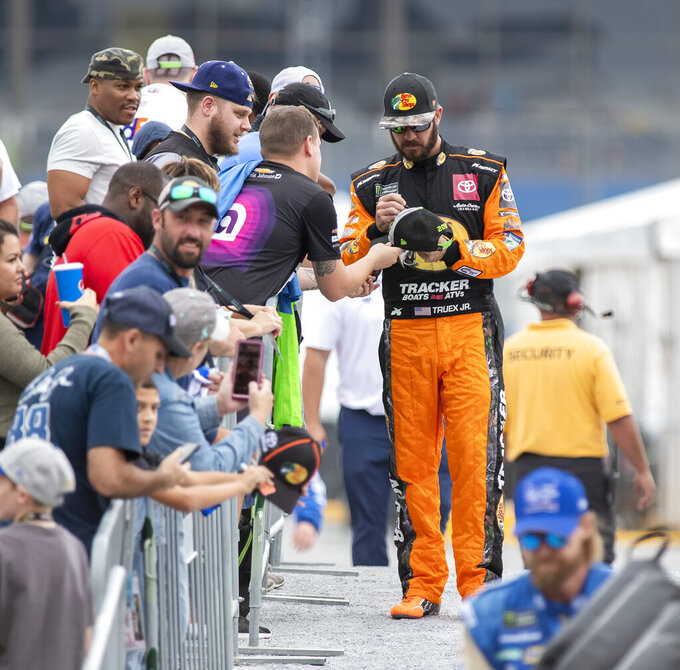 Martin Truex Jr., right, gives an autograph at the Drydene 400 - Monster Energy NASCAR Cup Series playoff auto race, Sunday, Oct. 6, 2019, at Dover International Speedway in Dover, Del. (AP Photo/Jason Minto)