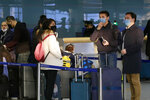 Passengers wearing masks as a precaution against a new coronavirus line up to check in for a flight to Vladivostok, Russia, at the Pyongyang International Airport in Pyongyang, North Korea, Monday, March 9, 2020. (AP Photo/Jon Chol Jin)