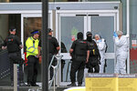 Police and forensic officers outside the Arndale Centre in Manchester, England, Friday Oct. 11, 2019, after a stabbing incident at the shopping center that left four people injured. Greater Manchester Police say a man in his 40s has been arrested on suspicion of serious assault. He had been taken into custody. (Peter Byrne/PA via AP)