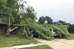 A tree fell across vehicles at a home in West Des Moines, Iowa, after a severe thunderstorm moved across Iowa on Monday Aug. 10, 2020, downing trees, power lines and damaging buildings. (AP Photo/David Pitt)