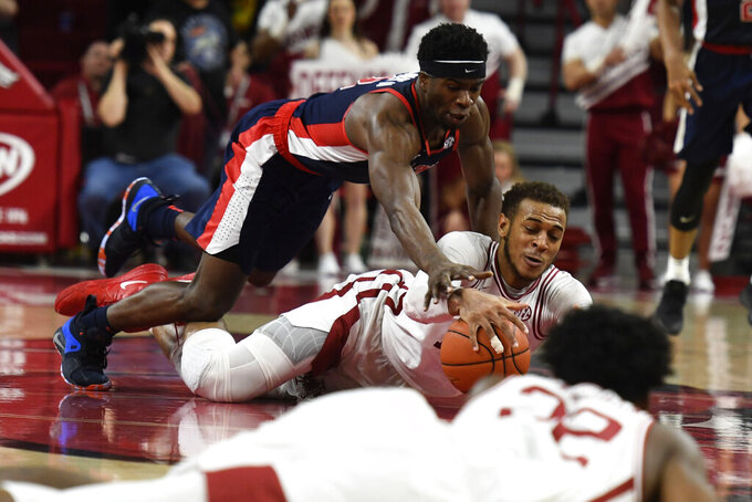 Arkansas forward Daniel Gafford (10) and Mississippi guard Terence Davis (3) dive for the ball on a scramble for possession in the final minute during the second half of an NCAA college basketball game, Saturday, March 2, 2019 in Fayetteville, Ark. The result of the play was a jump ball leading to an Arkansas possession that helped Arkansas hold on to the lead to defeat Mississippi. (AP Photo/Michael Woods)