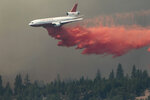 FILE - In this Monday, Aug. 20, 2012, file photo, a DC-10 drops fire retardant on the Ponderosa Fire near Paynes Creek, Calif. A McClatchy analysis reveals more than 350,000 Californians live in towns and cities that exist almost entirely within